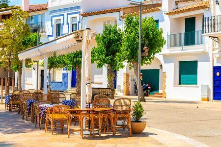 Restaurant tables on street of small fishing village of Llafranc, Costa Brava, Spain Stock Photo