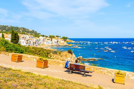 Couple of tourists sitting on coastal promenade in Calella de Palafrugell, scenic fishing village with small castle and sandy beach with clear blue water, Costa Brava, Catalonia, Spain