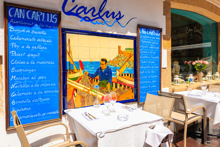 TOSSA DE MAR, SPAIN - JUN 6, 2019: Restaurant tables in beautiful old town of Tossa de Mar which is a seaside resort on Costa Brava, Spain.