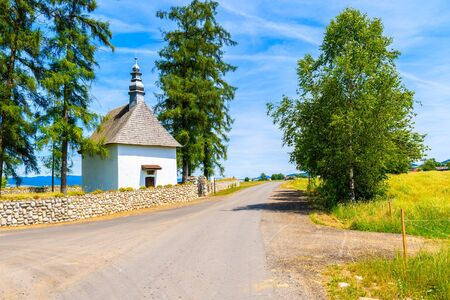 White small church on rural road in Tatra Mountains on sunny summer day, Poland