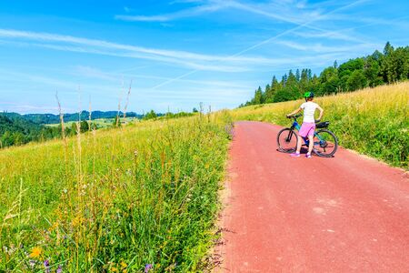 Young woman standing with bike on cycling way in green summer landscape near Czorsztynskie lake and Niedzica village, Pieniny Mountains, Poland
