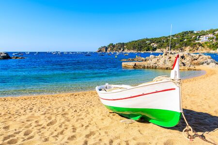 Traditional fishing boat on beach in Port Bo, old town of Calella de Palafrugell village, Costa Brava, Spain Stok Fotoğraf