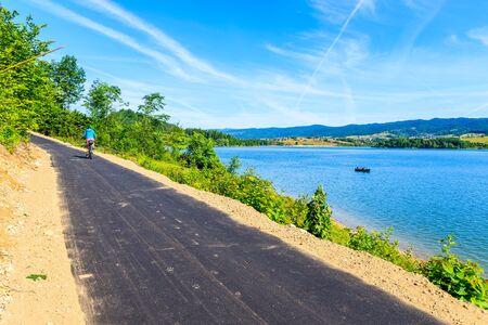 Young woman riding bike on cycling way along Czorsztynskie lake near Niedzica village, Pieniny Mountains, Poland Reklamní fotografie