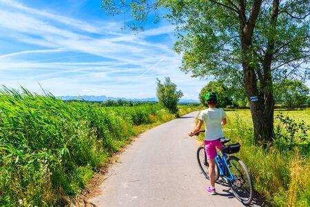 Young woman riding bike on cycling way along green fields near Czorsztynskie lake and Nowy Targ, Tatra Mountains, Poland Reklamní fotografie