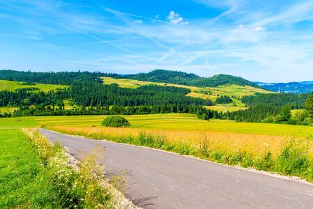 Cycling road around Tatra Mountains and green fields on summer day with beautiful blue sky, Poland