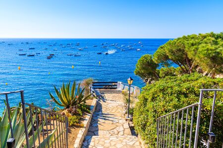 Walkway to viewpoint over sea with boats in Calella de Palafrugell fishing village, Costa Brava, Catalonia, Spain