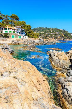 Rocks on sea coast with white fishing house in background near Llarfanc town, Costa Brava, Spain Reklamní fotografie