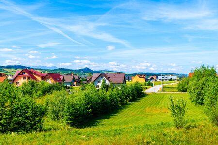 Houses in Frydman village in Pieniny Mountains near Czorsztynskie lake on sunny summer day, Poland
