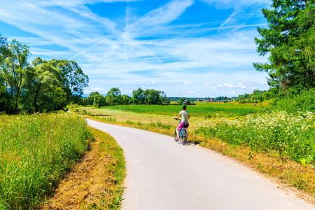 Young woman cyclist standing on cycling way along Dunajec river and looking at green farming fields near Czorsztynskie lake, Pieniny Mountains, Poland Reklamní fotografie