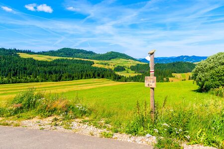 Cycling road around Tatra Mountains and green fields on summer day with beautiful blue sky, sing on wooden post Cmentarz Zydowski means Jewish Cemetary, Poland