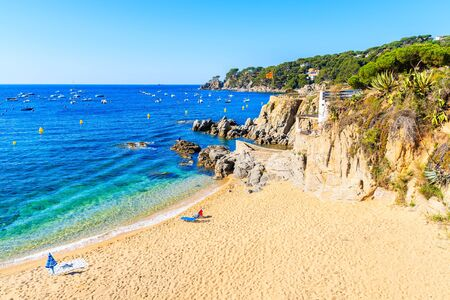 Sun chairs and umbrella on picturesque beach in Calella de Palafrugell fishing village, Costa Brava, Catalonia, Spain