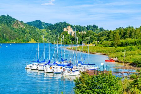 Sailing boats in port on shore of Czorsztynskie lake with castle in background on beautiful summer day in Niedzica village, Pieniny Mountains, Poland