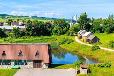 Houses and church in Frydman village in Pieniny Mountains near Czorsztynskie lake on sunny summer day, Poland
