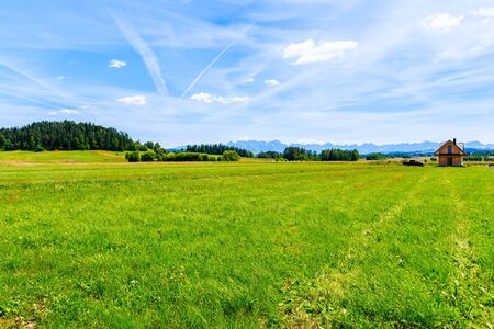 Small wooden house on green field and view of Tatra Mountains on summer day, Poland