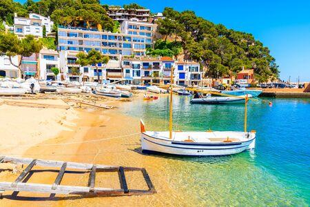 Traditional white fishing boat on beach in Llafranc port, Costa Brava, Spain
