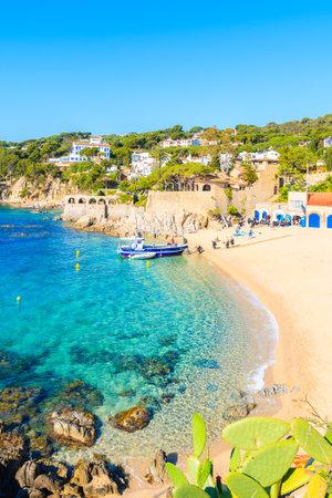 CALELLA DE PALAFRUGELL, SPAIN - JUN 2, 2019: Divers walking to boat on picturesque beach in Calella de Palafrugell fishing village, Costa Brava, Catalonia, Spain.