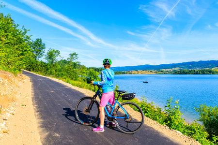 NIEDZICA VILLAGE, POLAND - JUN 29, 2019: Young woman standing with bike on cycling way Velo Dunajec in green summer landscape near Czorsztynskie lake, Pieniny Mountains, Poland