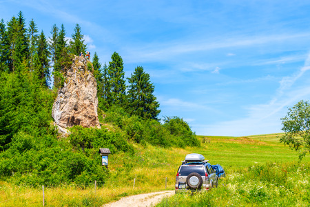 TATRA MOUNTAINS, POLAND - JUN 29, 2019: Two men on top of a rock after climbing it on sunny summer day, green hills near Nowy Targ, Poland.