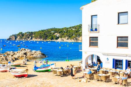 CALELLA DE PALAFRUGELL, SPAIN - JUN 2, 2019: Restaurant and colorful fishing boats on picturesque beach in Calella de Palafrugell village, Costa Brava, Catalonia, Spain.