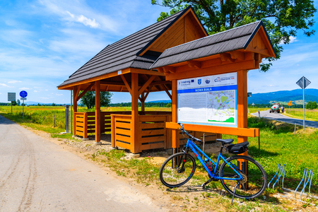 TATRA MOUNTAINS, POLAND - JUN 29, 2019: Bike parking in front of map with cycling ways in Tatra Mountains, Poland. Reklamní fotografie - 128079555