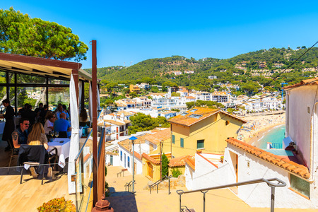 LLAFRANC TOWN, SPAIN - JUN 1, 2019: People sitting under shade on terrace of typical restaurant in Llafranc town, Costa Brava, Spain.