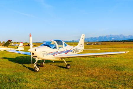 TATRA MOUNTAINS, POLAND - JUN 29, 2019: Small airplane on green airfield on Nowy Targ airport near Tatra Mountains, Poland.