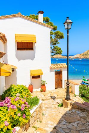 White houses decorated with flowers and path to beach in Sa Tuna fishing village, Costa Brava, Catalonia, Spain