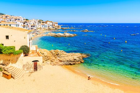 Young woman sitting on sandy beach in picturesque fishing village of Calella de Palafrugell, Catalonia, Spain