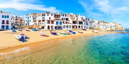 Panoramic view of fishing boats on beach in Port Bo with colorful houses of old town of Calella de Palafrugell, Costa Brava, Catalonia, Spain