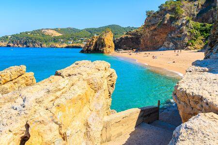 Path to Cala Moreta beach and view of blue sea and rocks, Costa Brava, Catalonia, Spain Фото со стока - 130816057