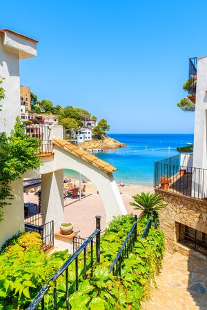 Walking path to beach in Sa Tuna village with colorful houses on shore, Costa Brava, Catalonia, Spain