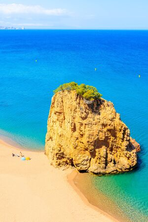 Rock in sea known as Isla Roja on beautiful Cala Moreta beach and view of blue sea, Costa Brava, Catalonia, Spain Фото со стока - 130816084