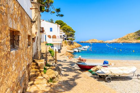 Fishing boats on beach in Sa Tuna village with colorful houses on shore, Costa Brava, Catalonia, Spain