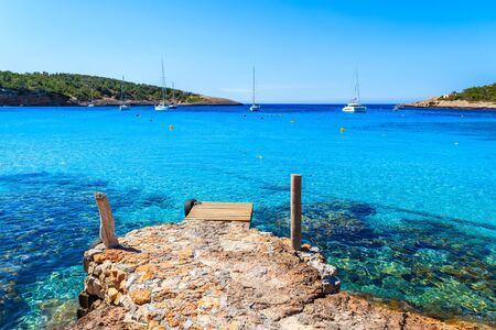 Pier and azure sea water in beautiful bay of Cala Portinatx, Ibiza island, Spain