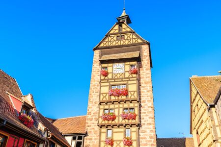 Beautiful church tower in old part of Riquewihr village which is located on famous wine route in Alsace region of France. Stockfoto