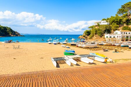 Catamaran and fishing boats on beach in beautiful Sa Riera village, Costa Brava, Catalonia, Spain Фото со стока - 130816095