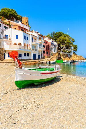 Fishing boat on beach in Sa Tuna village with colorful houses, Costa Brava, Catalonia, Spain