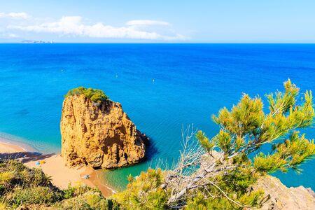 Rock in sea known as Isla Roja on beautiful Cala Moreta beach and view of blue sea, Costa Brava, Catalonia, Spain Фото со стока
