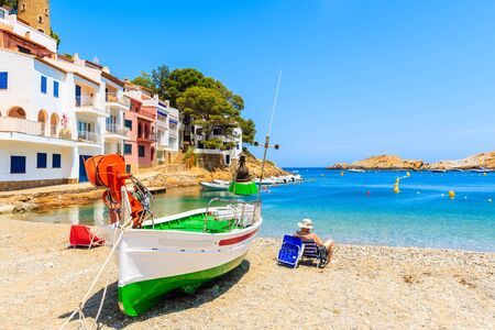 Fishing boat on beach in Sa Tuna village with colorful houses on shore, Costa Brava, Catalonia, Spain Фото со стока - 130816110