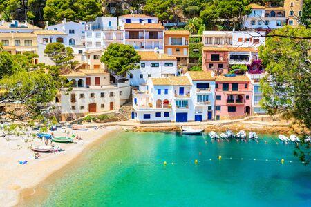 View of beach in Sa Tuna fishing village with colorful houses on shore, Costa Brava, Catalonia, Spain Фото со стока - 130816123