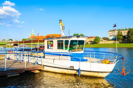 Tourist boat anchoring on Vistula river and Wawel castle in background at sunset time, Krakow, Poland