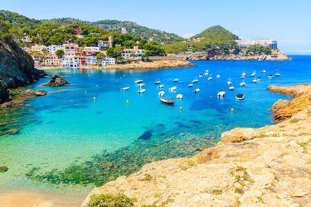 View of beach in Sa Tuna fishing village with boats in sea bay, Costa Brava, Catalonia, Spain Standard-Bild - 130816137