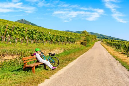 Young woman cyclist resting on bench along Alsatian Wine Route near Hunawihr village, France