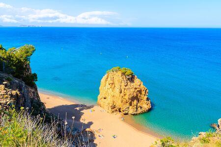 Rock in sea known as Isla Roja on beautiful Cala Moreta beach and view of blue sea, Costa Brava, Catalonia, Spain Фото со стока - 130816101