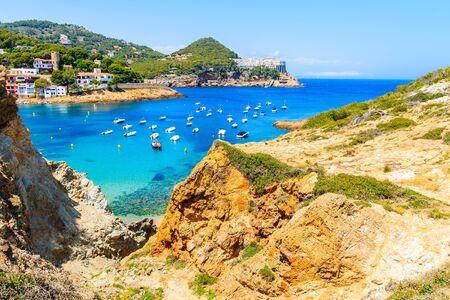 View of beach in Sa Tuna fishing village with boats in sea bay, Costa Brava, Catalonia, Spain Фото со стока - 130816104