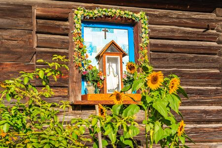 Wayside shrine with sunflowers located in old wooden house in small village near Nowy Sacz city, Poland Reklamní fotografie