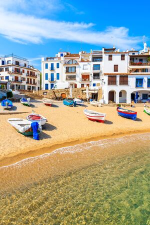 Fishing boats on beach in Port Bo with colorful houses of old town of Calella de Palafrugell in background, Catalonia, Spain Standard-Bild - 130816129