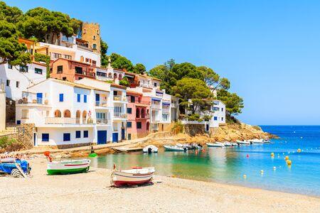 Fishing boats on beach in Sa Tuna village with colorful houses on shore, Costa Brava, Catalonia, Spain Фото со стока - 130816135
