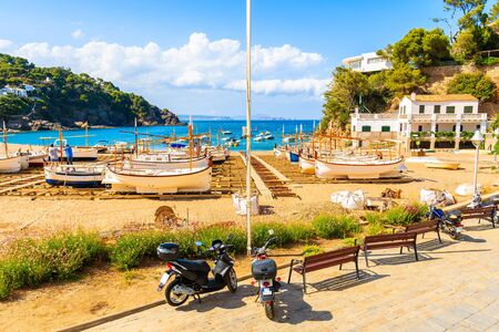 Scooters parking on coastal promenade and view of fishing boats on beach in beautiful Sa Riera village, Costa Brava, Catalonia, Spain