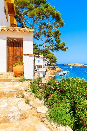 Wooden door of a white house decorated with flowers and view of beach in Sa Tuna fishing village, Costa Brava, Catalonia, Spain